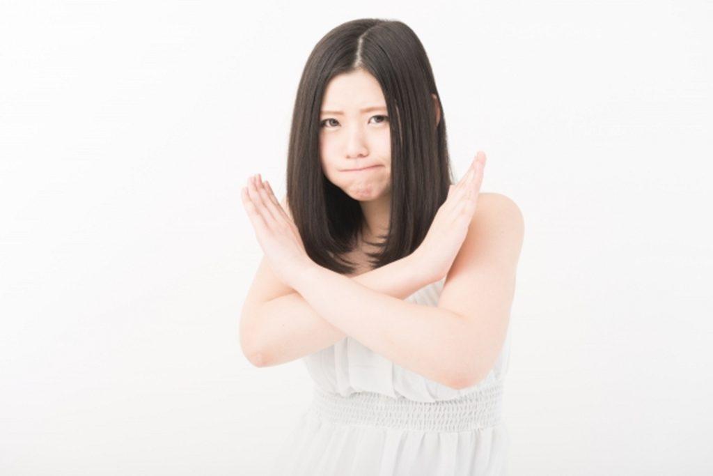 腕をクロスさせてバツ印を作る女性