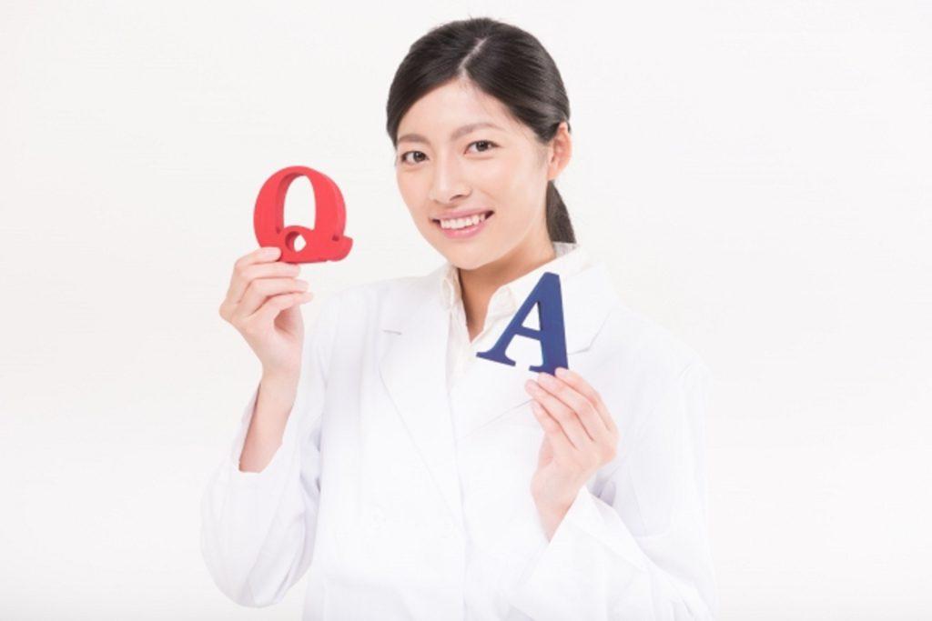 Q&Aの札を持つ女医