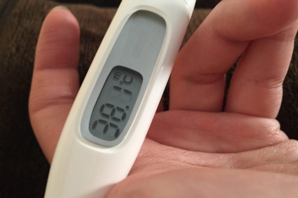 手に持った体温計が38度
