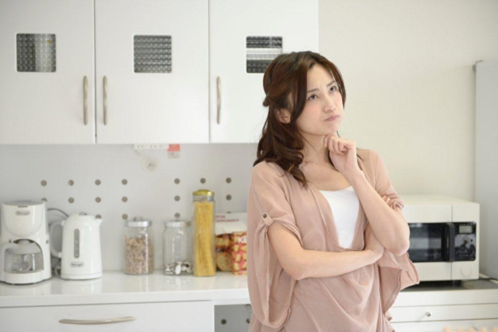 キッチンに立って考える女性