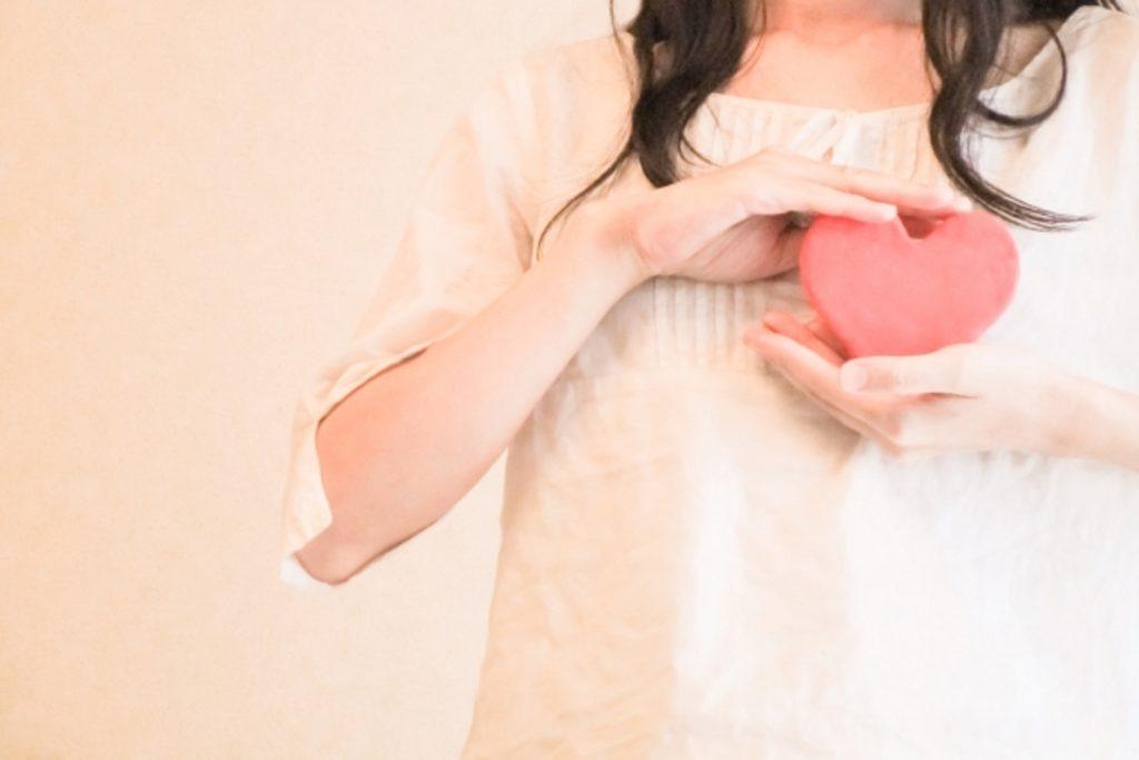 胸の前でハートを包む女性